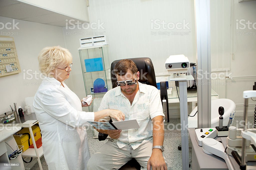 Doctor,examining a patient in ophthalmology clinic royalty-free stock photo