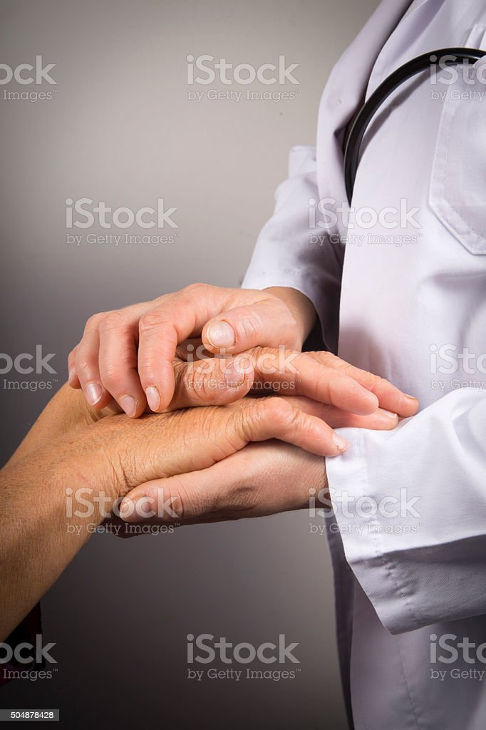Doctor/Nurse holding an elder patient's hand kindly stock photo