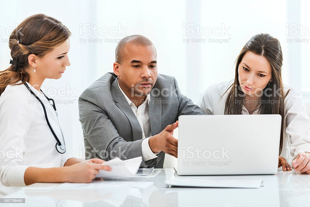Doctors and businessman using computer. stock photo