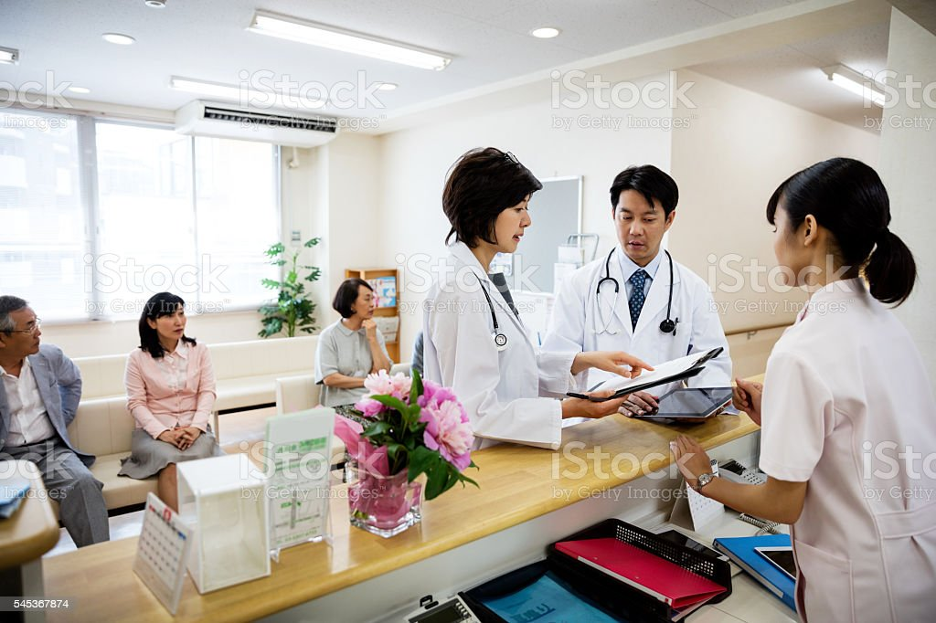 Doctors and nurse standing at reception with patients waiting in stock photo