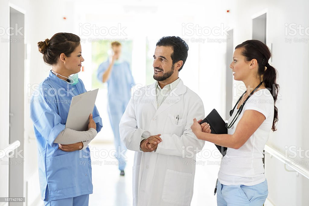 Doctors and nurse talking in hospital corridor royalty-free stock photo