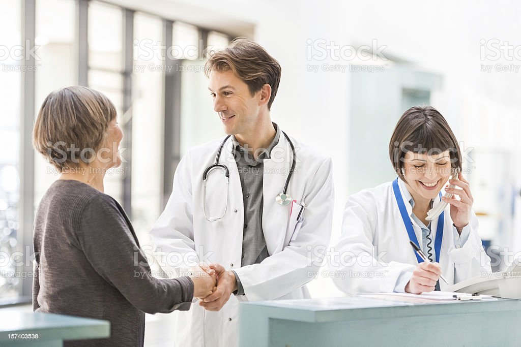 Doctors and Patient at Reception Desk stock photo