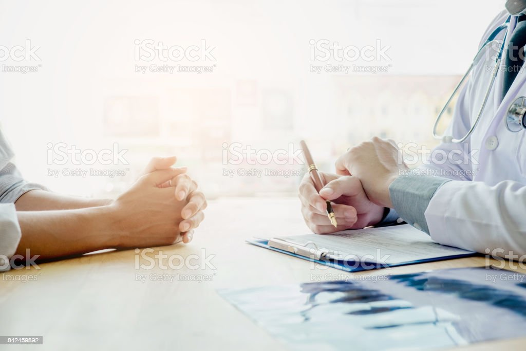 Doctors and patients sit and talk. At the table near the window in...