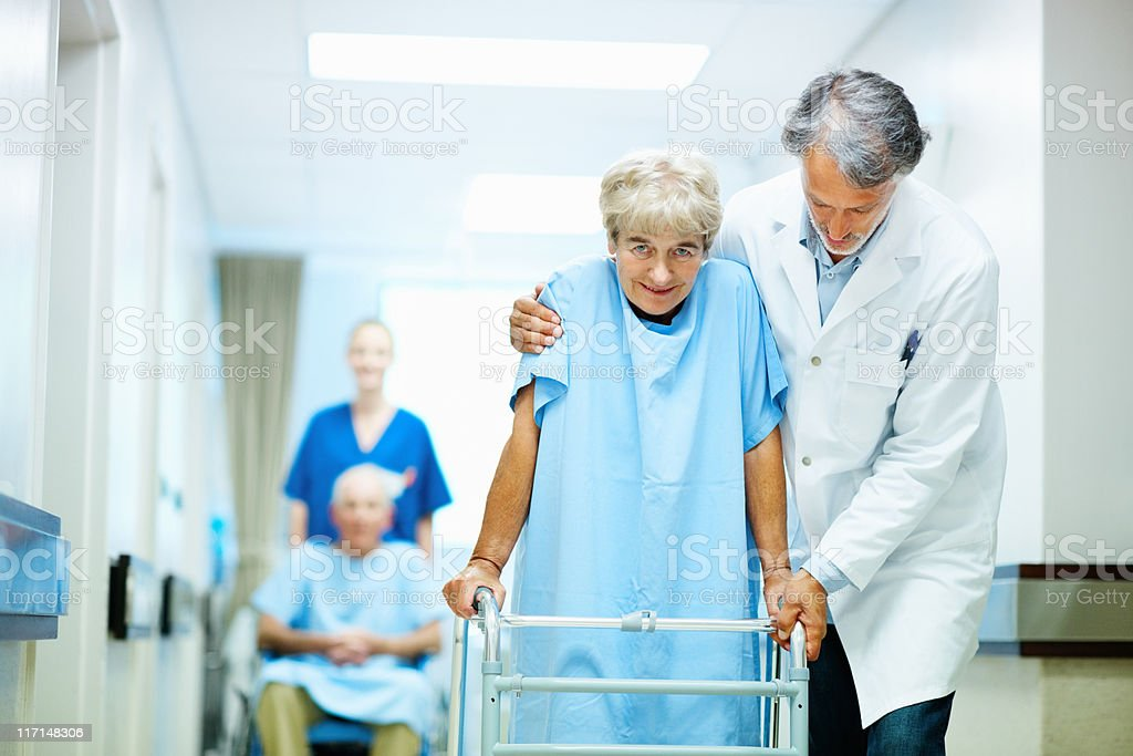 Doctors assisting patients with walker and wheelchair royalty-free stock photo