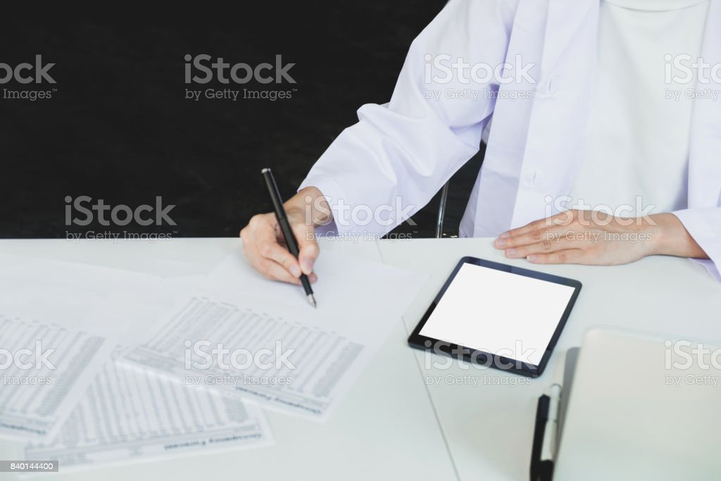 doctors being discussing patient history in an office pointing to a clipboard with document paper as they make a diagnosis or recommend on treatment stock photo