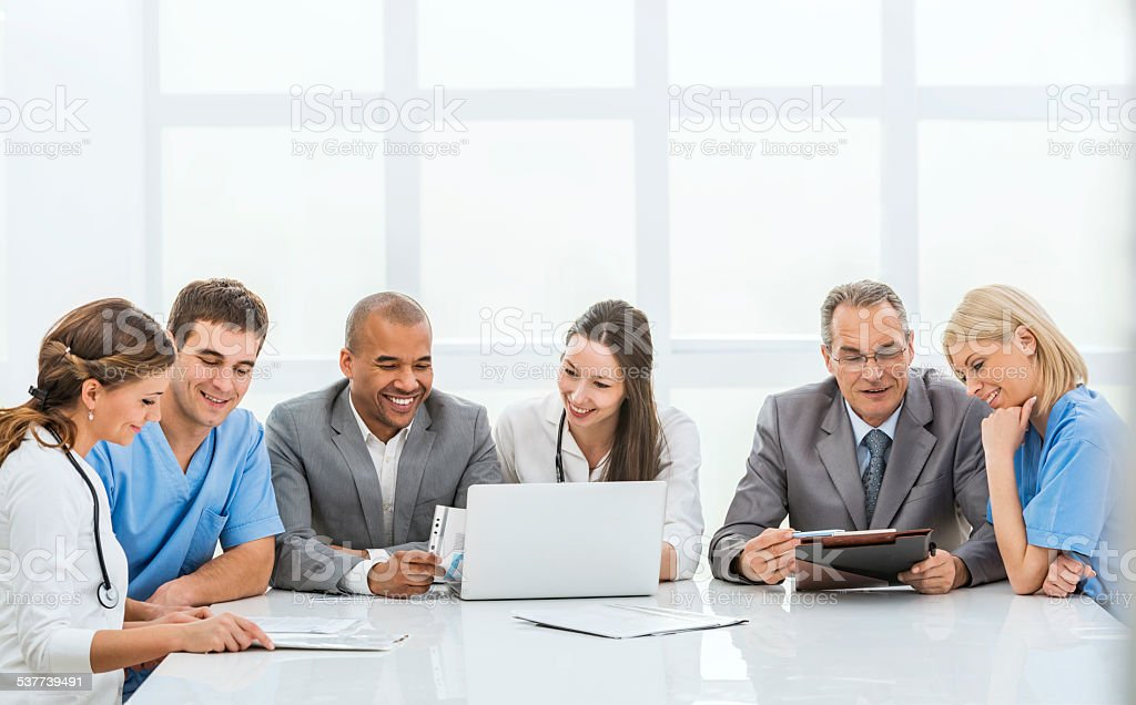 Doctors collaborating with a businessmen stock photo
