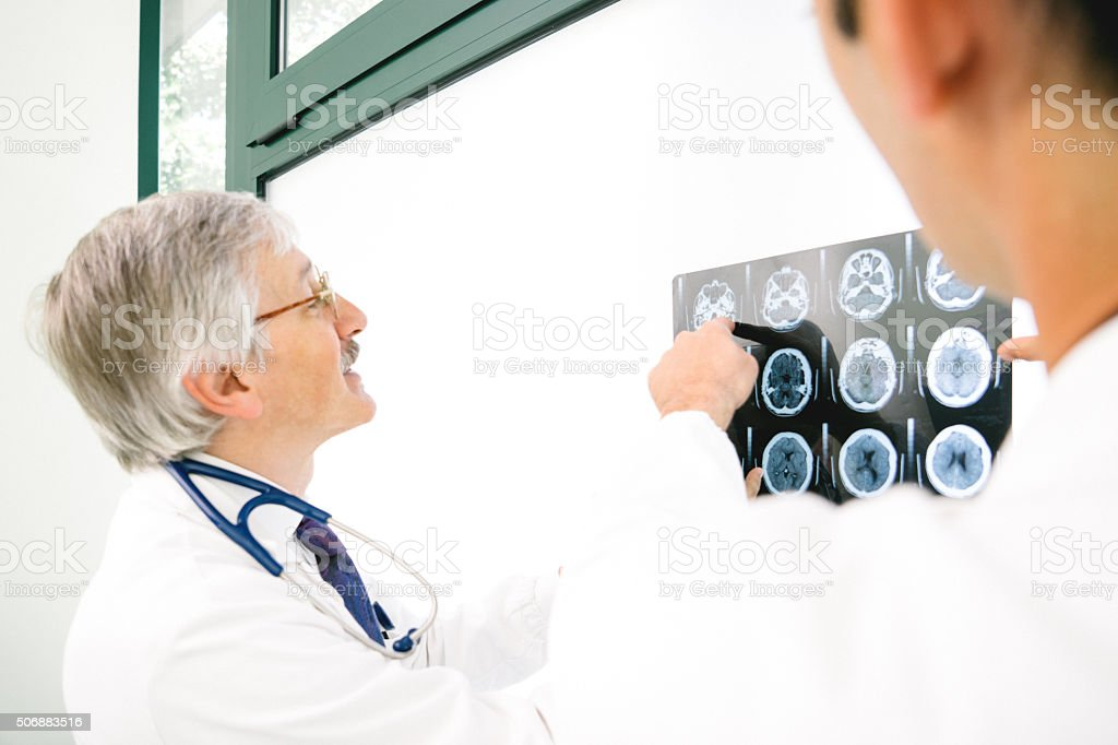 Doctors Consult Over An MRI Scan Of The Brain stock photo
