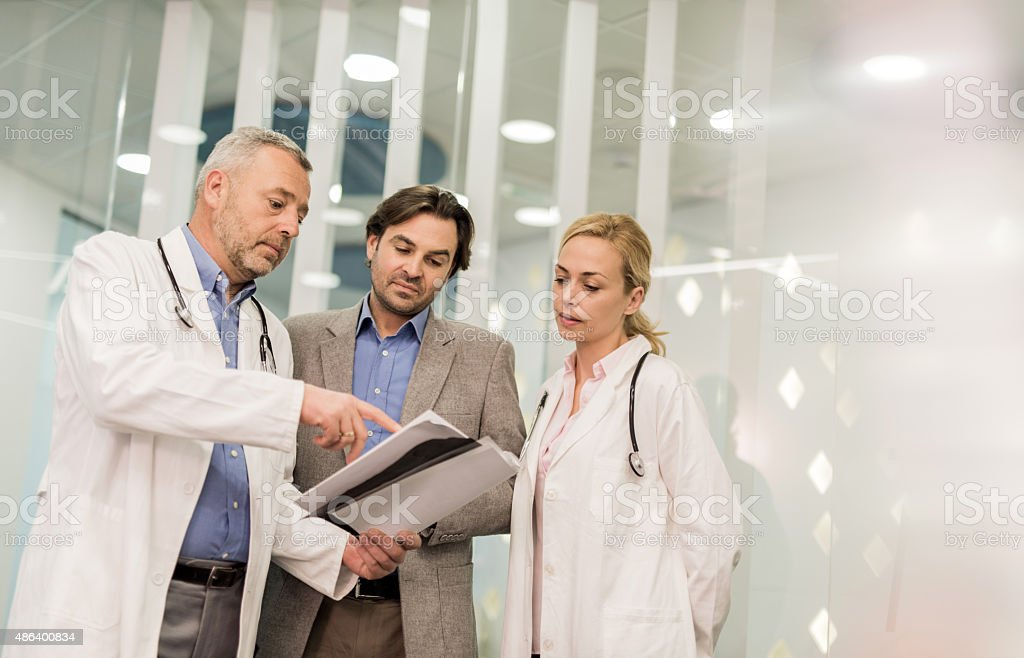 Doctors cooperating with a businessman while working on paperwork. stock photo