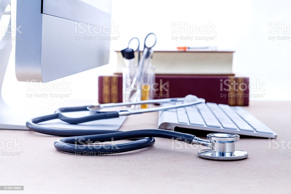 Doctor's desk with computer and medical textbook . stock photo