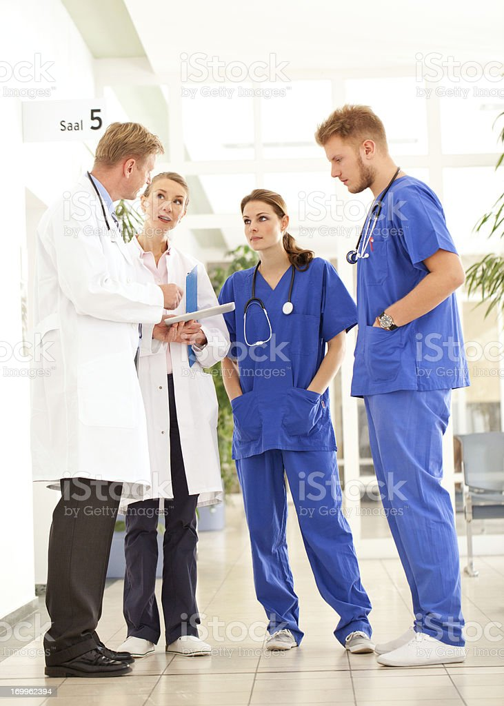 Doctors discussing around a digital tablet stock photo