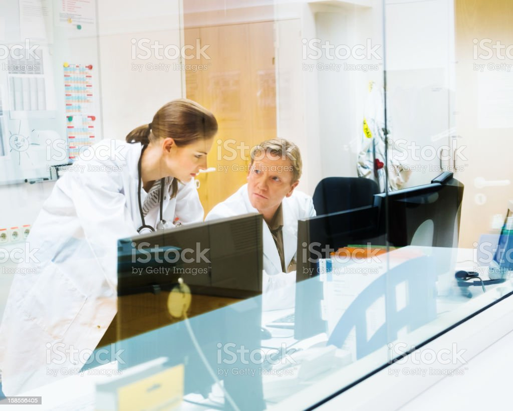 Doctors Discussing CAT Scans on Monitor stock photo