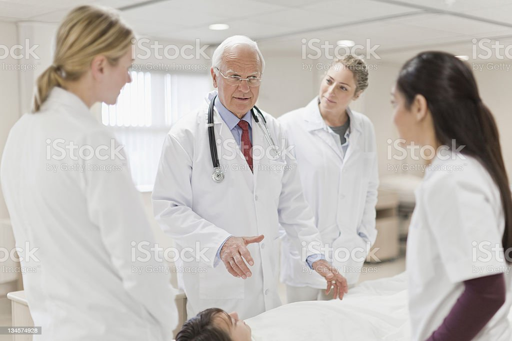 Doctors discussing patient in hospital stock photo