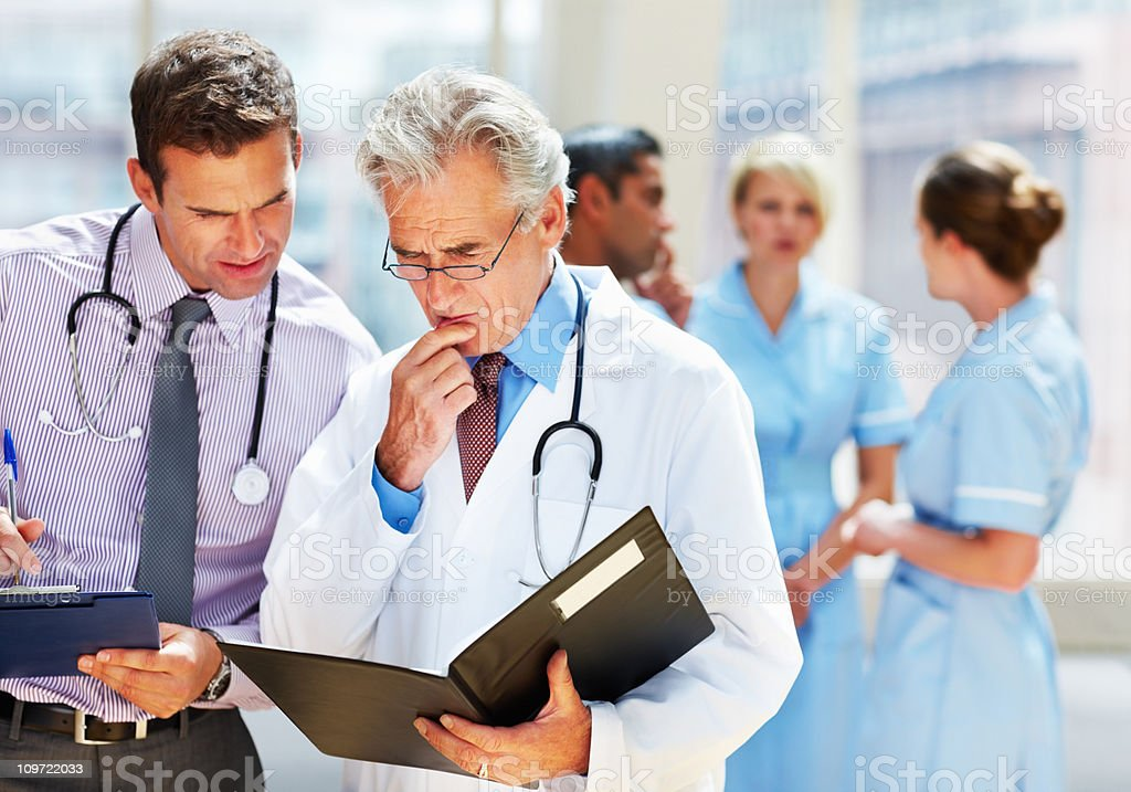 Doctors discussing schedule while their team in background royalty-free stock photo