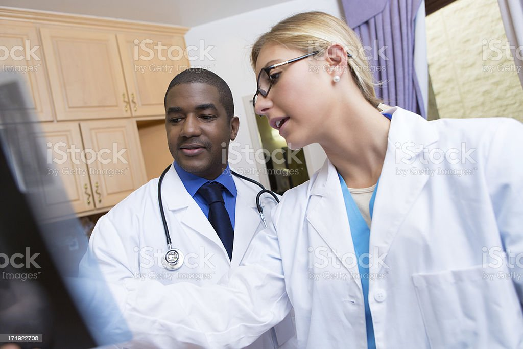 Doctors discussing x-ray records in patient room royalty-free stock photo