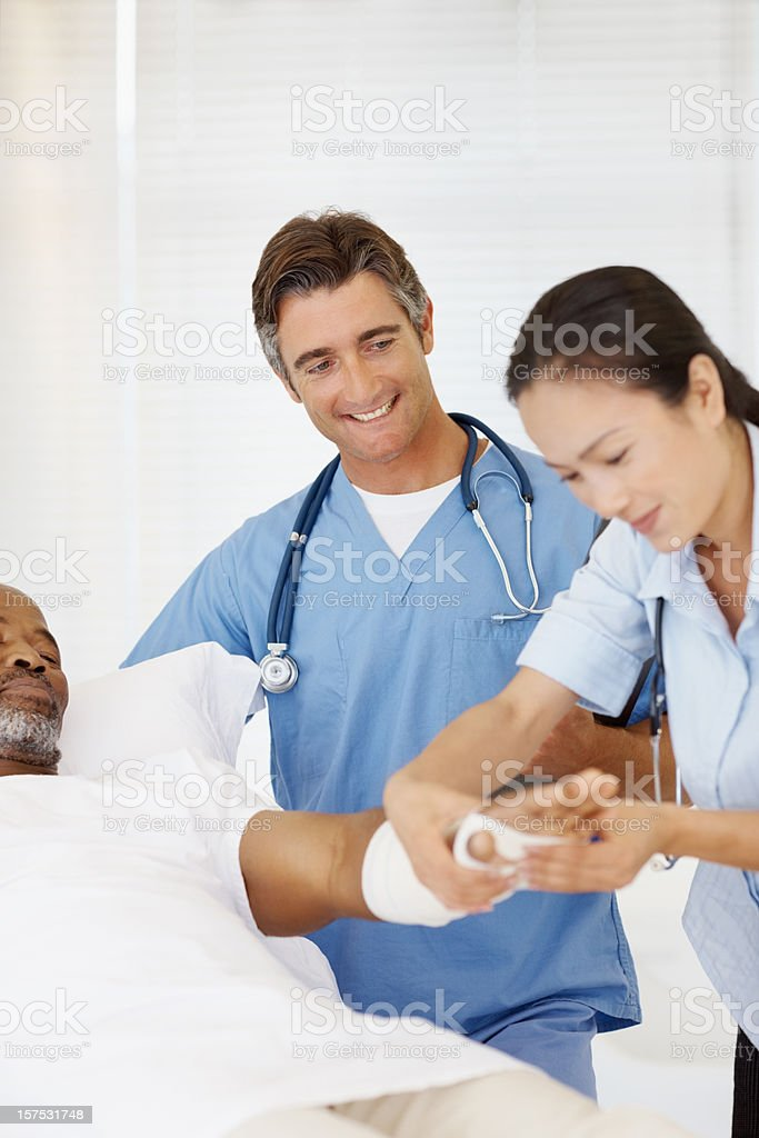 Doctors examining a man's bandaged hand royalty-free stock photo