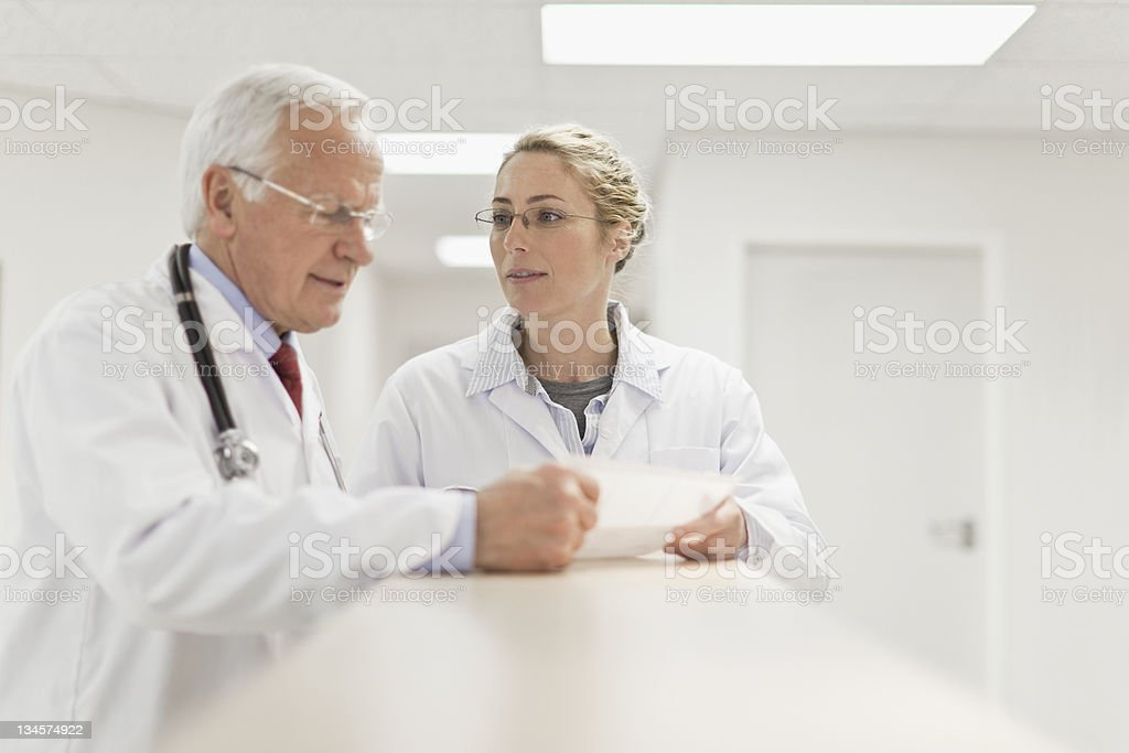 Doctors examining paperwork in hospital stock photo