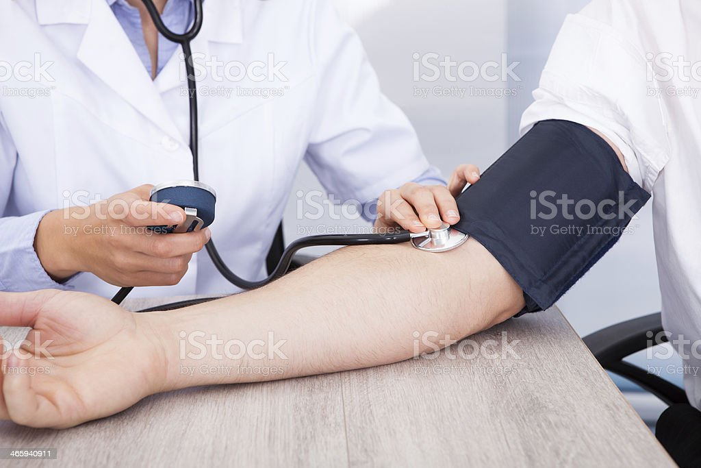 Doctor's Hand Checking Blood Pressure stock photo