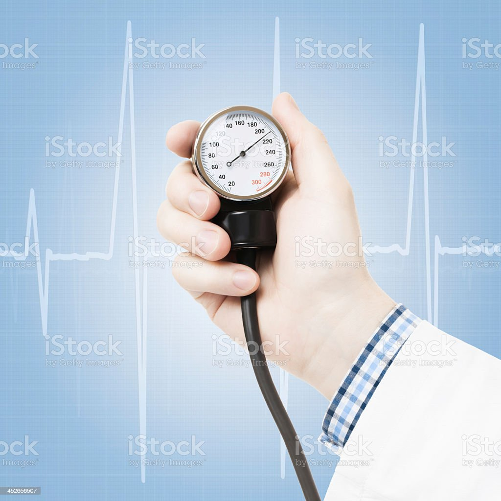 Doctor's hand holding blood pressure gauge on heartbeat back stock photo