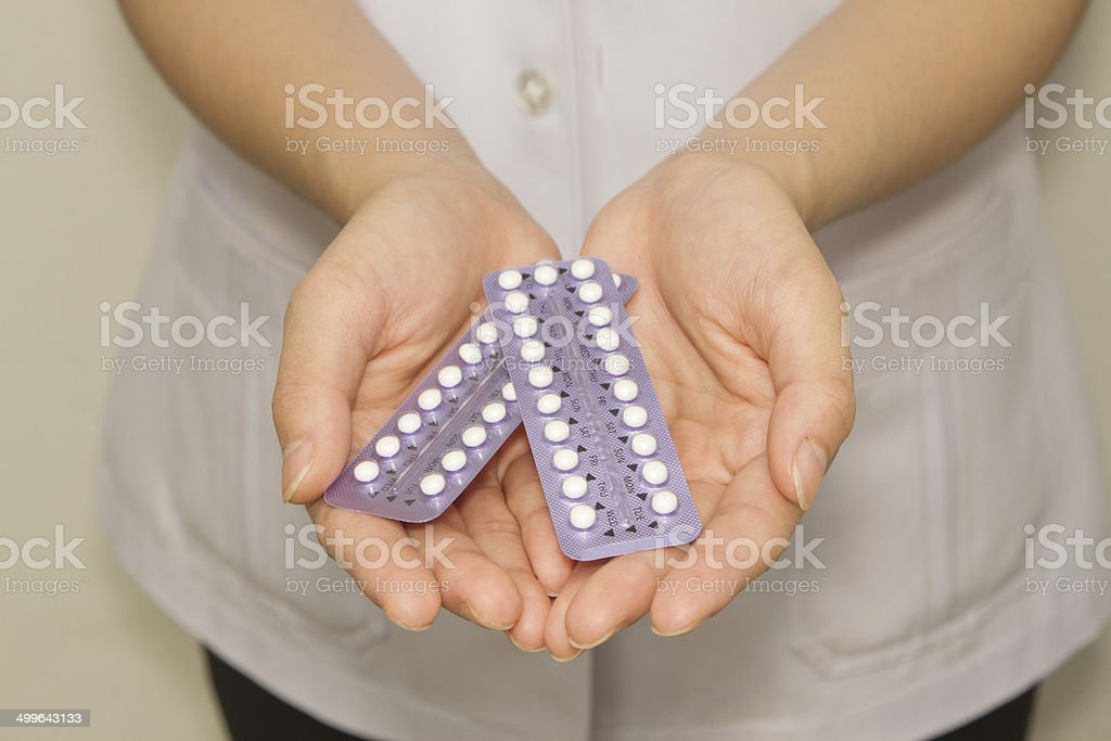 doctor's hand  holding the birth control pills stock photo