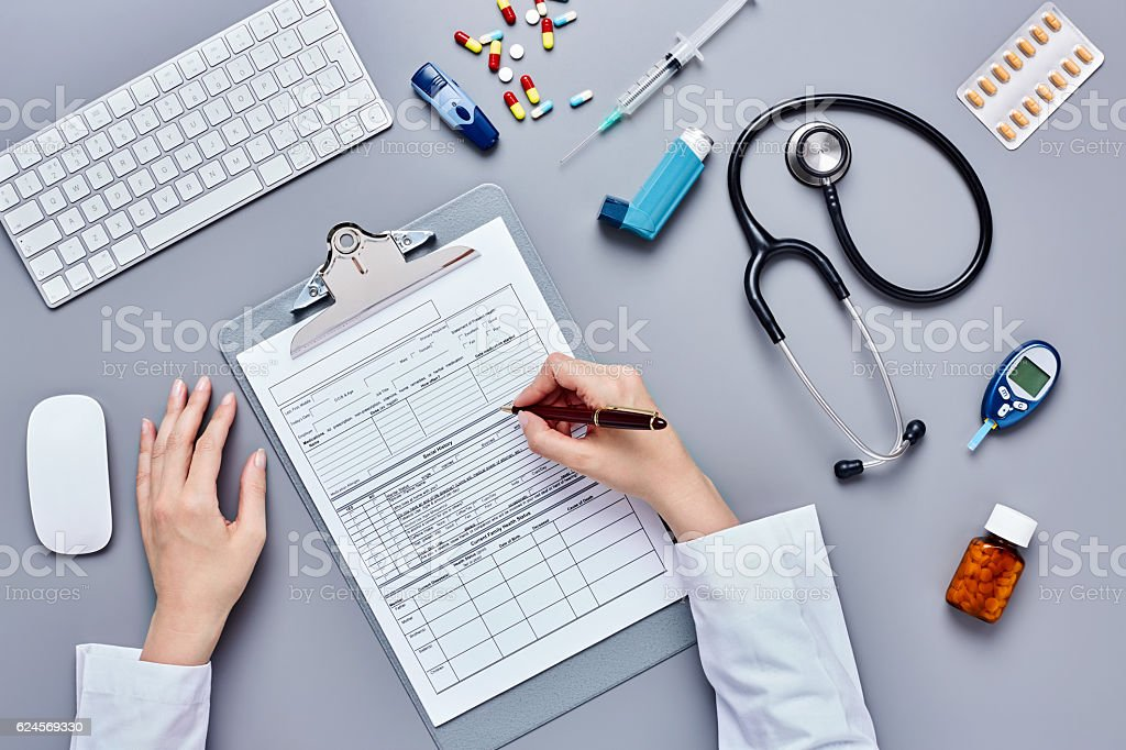 Doctor's hands filling patient information form by medical suppl stock photo