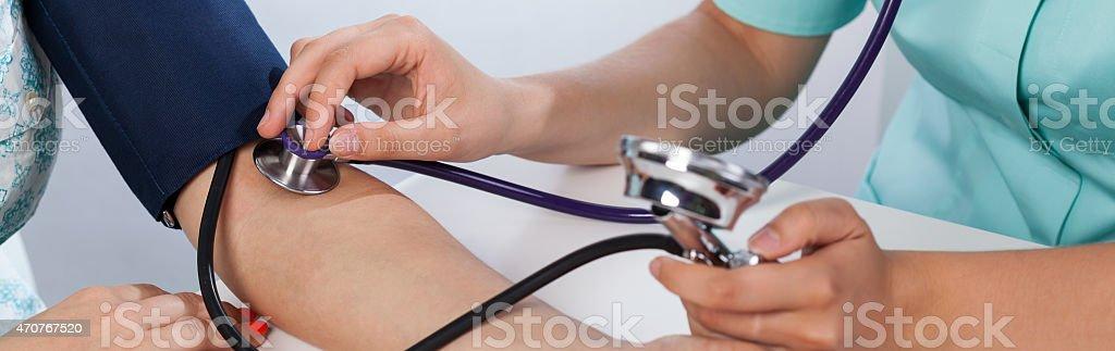 Doctor's hands measuring blood pressure stock photo