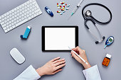 Doctor's hands using tablet with digitized pen by medical equipm