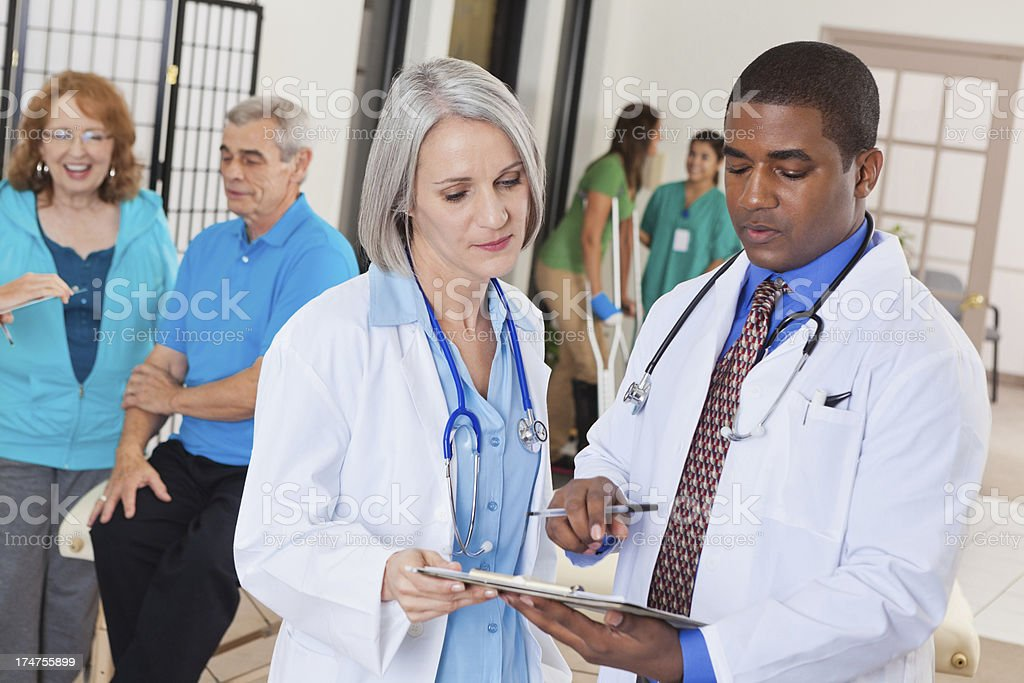 Doctors in busy rehabilitation hospital discussing patient forms royalty-free stock photo