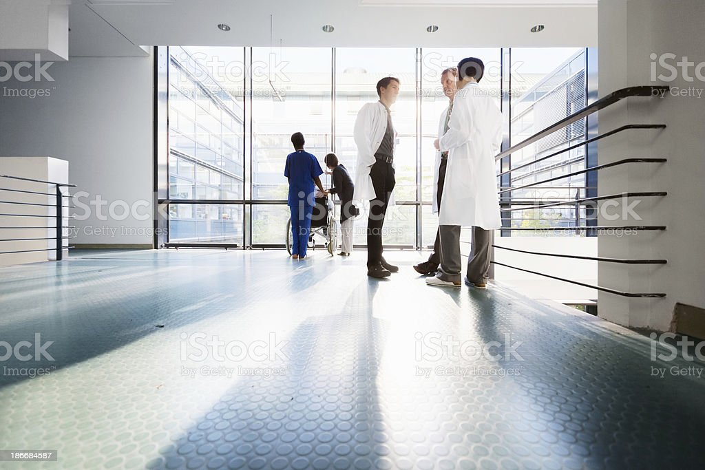 Three doctors discussing in corridor. Nurse with patient in...