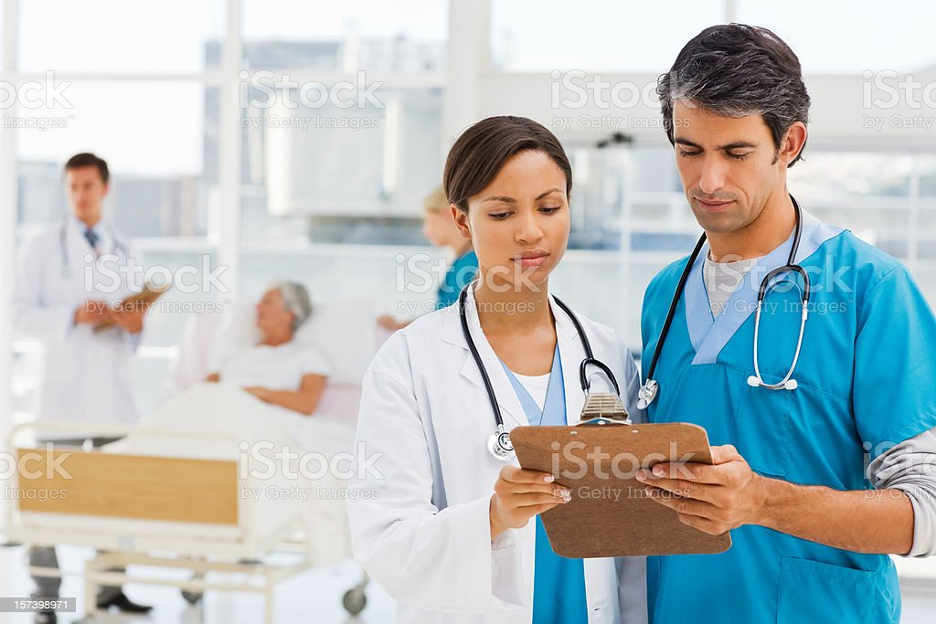 Doctors looking at reports with patient in background royalty-free stock photo