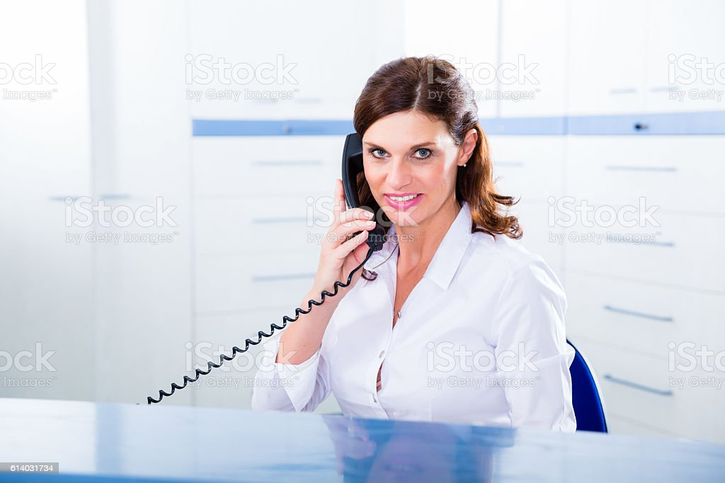 Doctors nurse with telephone in front desk stock photo