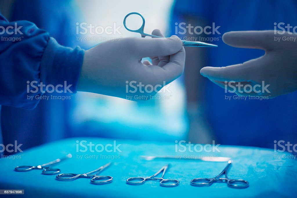 Doctors passing surgical tools in hospital operating room stock photo