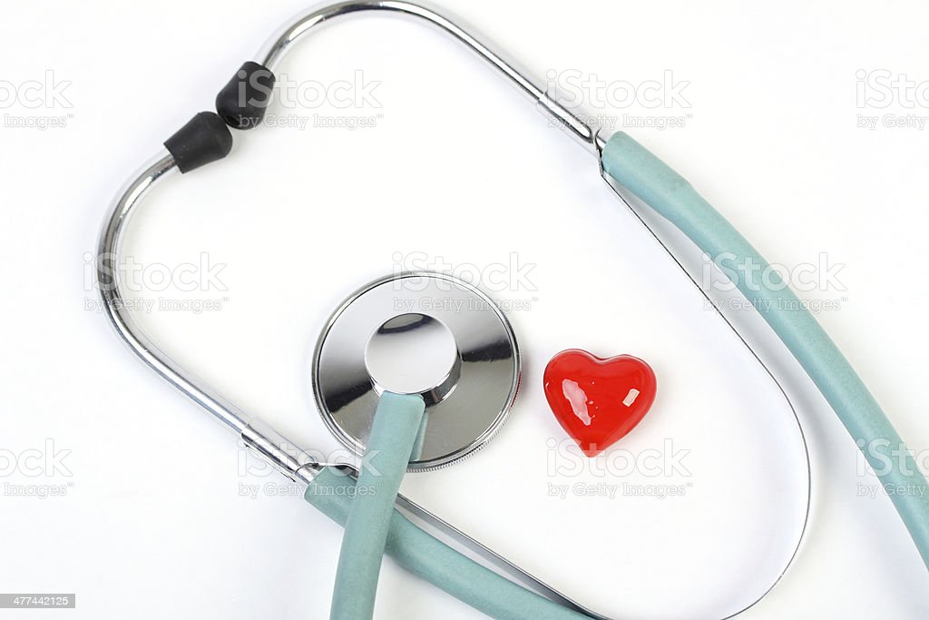 Doctors stethoscope and one small red heart stock photo