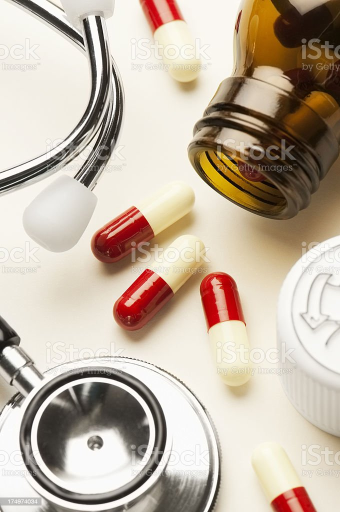 Doctors stethoscope with pill bottle and scattered pills royalty-free stock photo