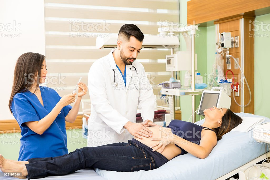 Doctors taking care of pregnant woman stock photo