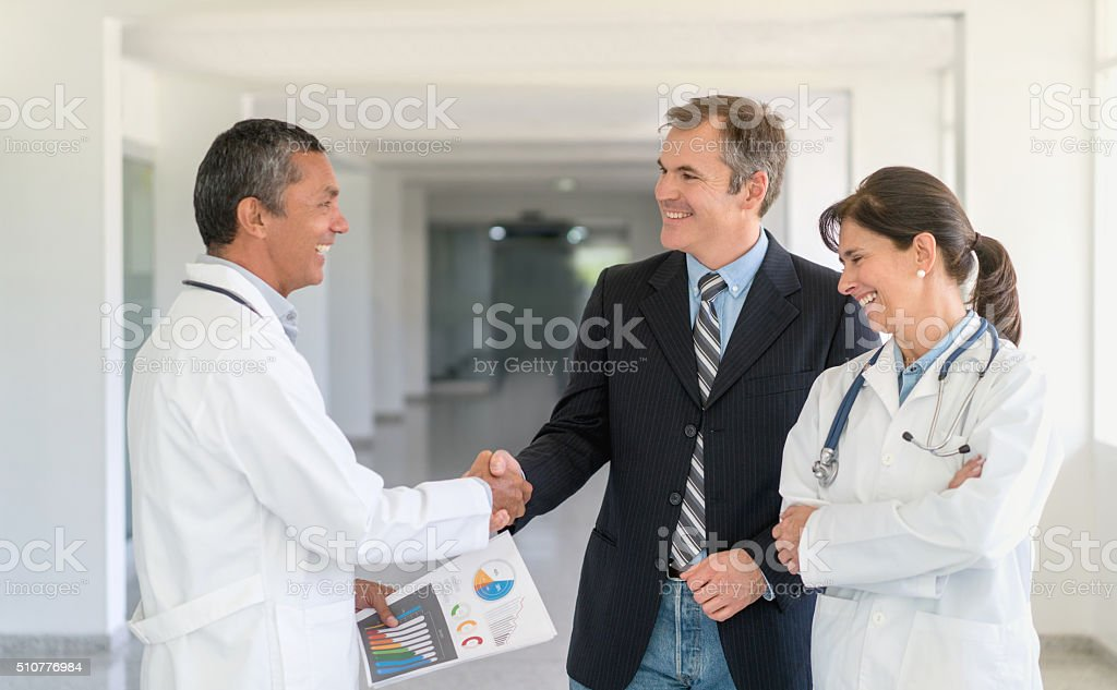 Doctors talking to business man about medical insurance and...