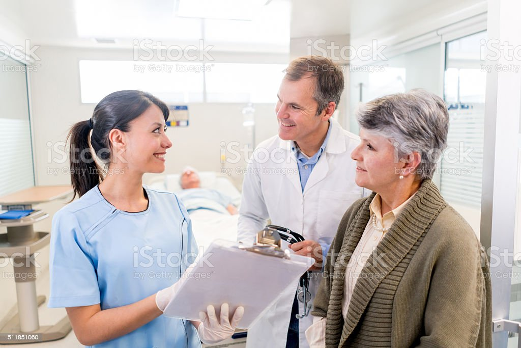 Doctors talking to pantient's family at the hospital stock photo