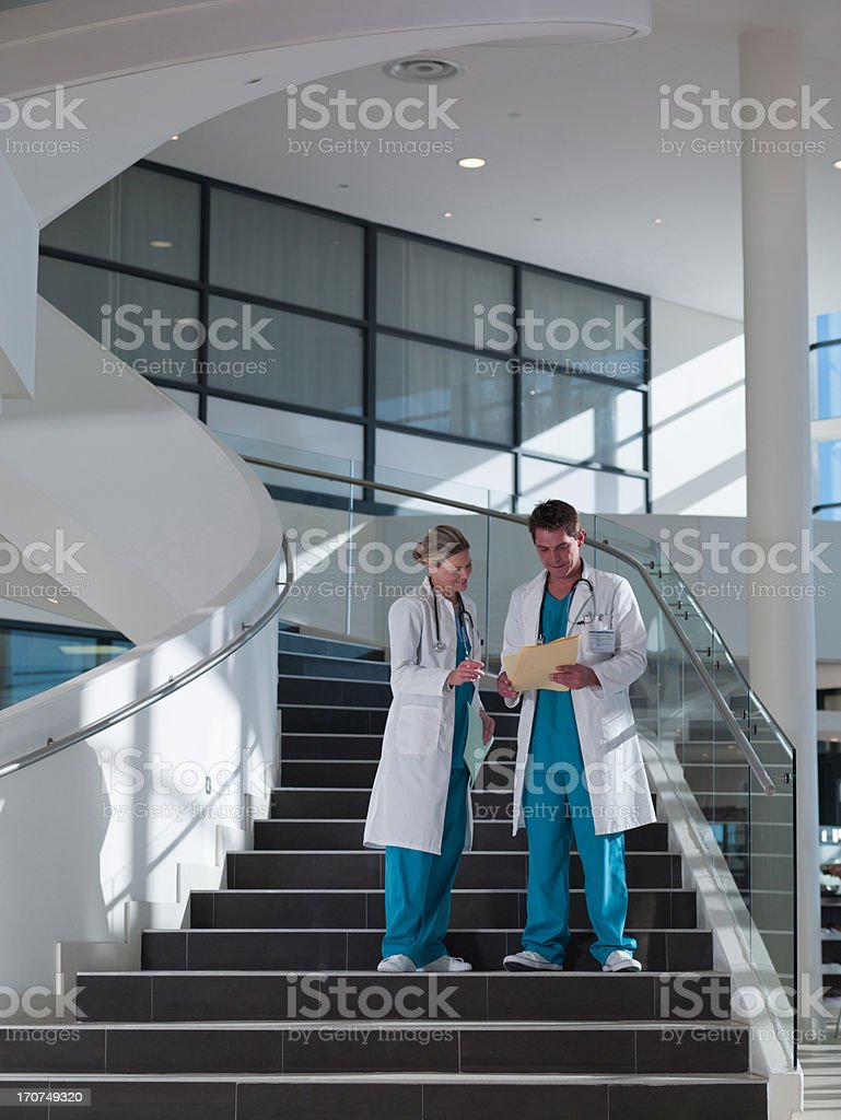 Doctors walking down staircase in hospital stock photo
