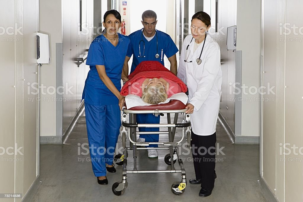 Doctors with patient on hospital trolley stock photo