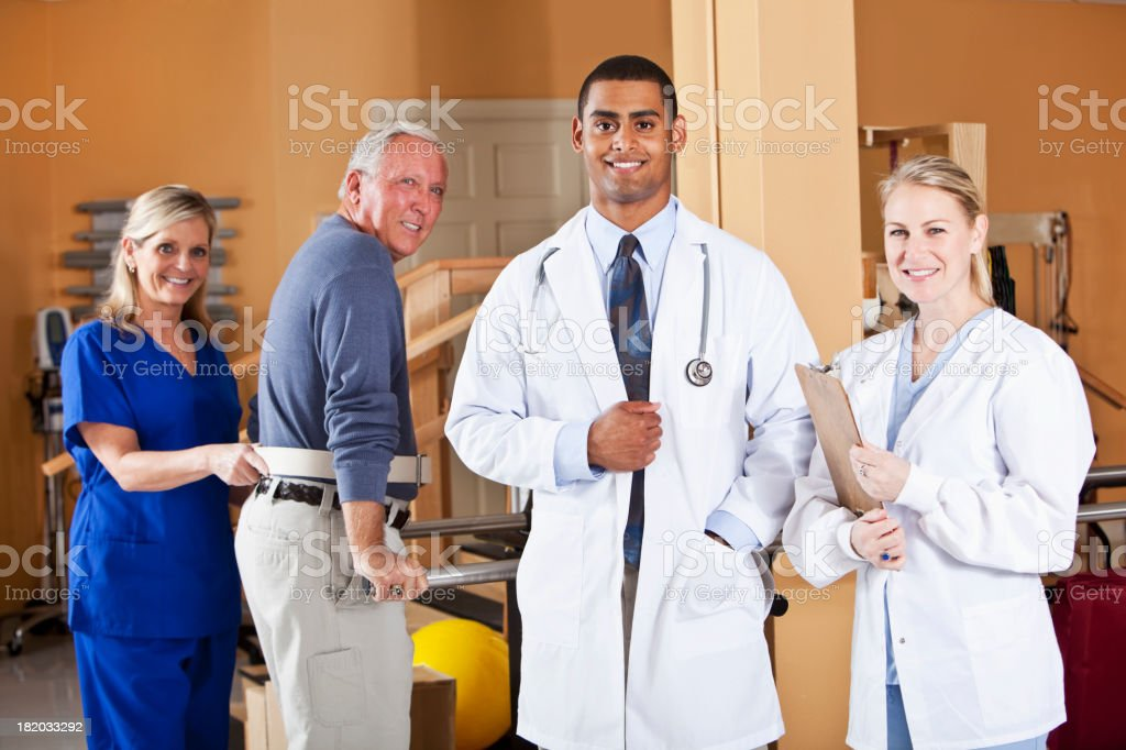 Doctors with physical therapy patient stock photo