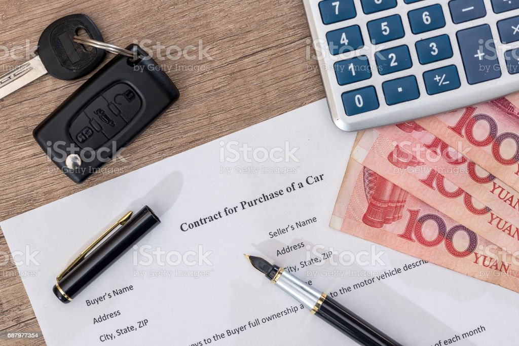 document, yuan bills, pen and car key on desk. stock photo