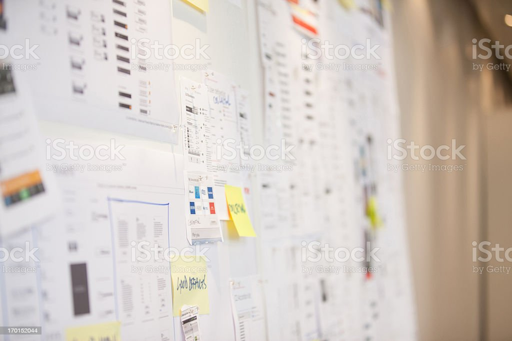 Documents and adhesive notes on wall in office stock photo