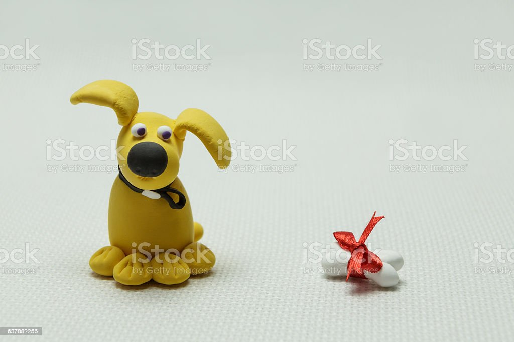 Dog a mongrel and a bone from plasticine stock photo
