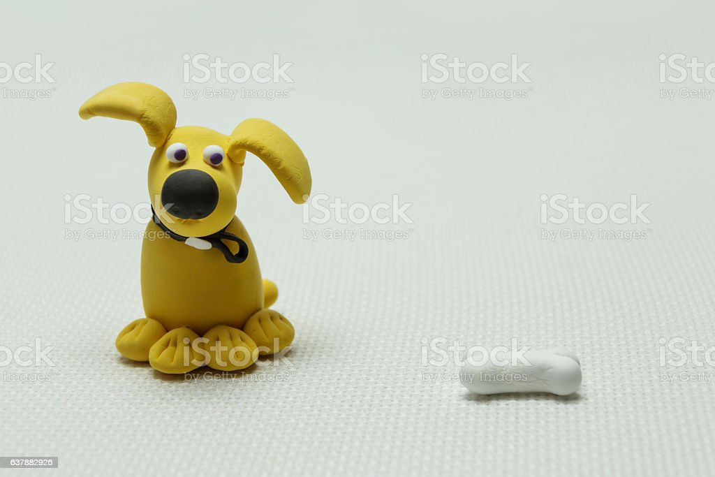 Dog and a bone from plasticine stock photo