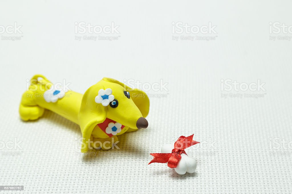 Dog and bone from plasticine tied up by a band stock photo