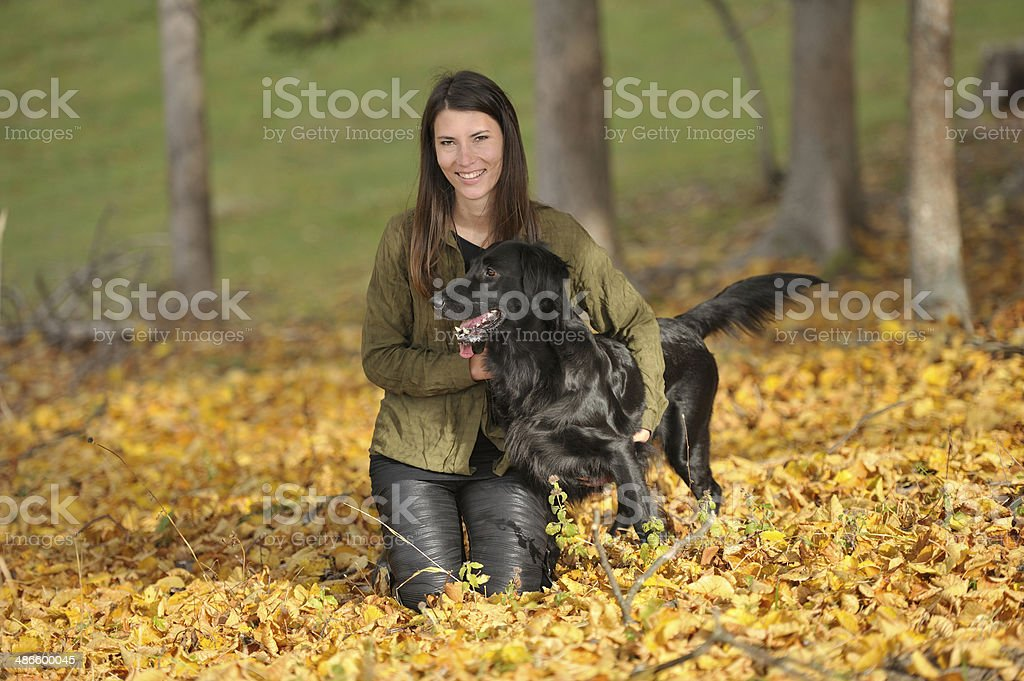 Dog and woman on autumn leaves with forest in background royalty-free stock photo