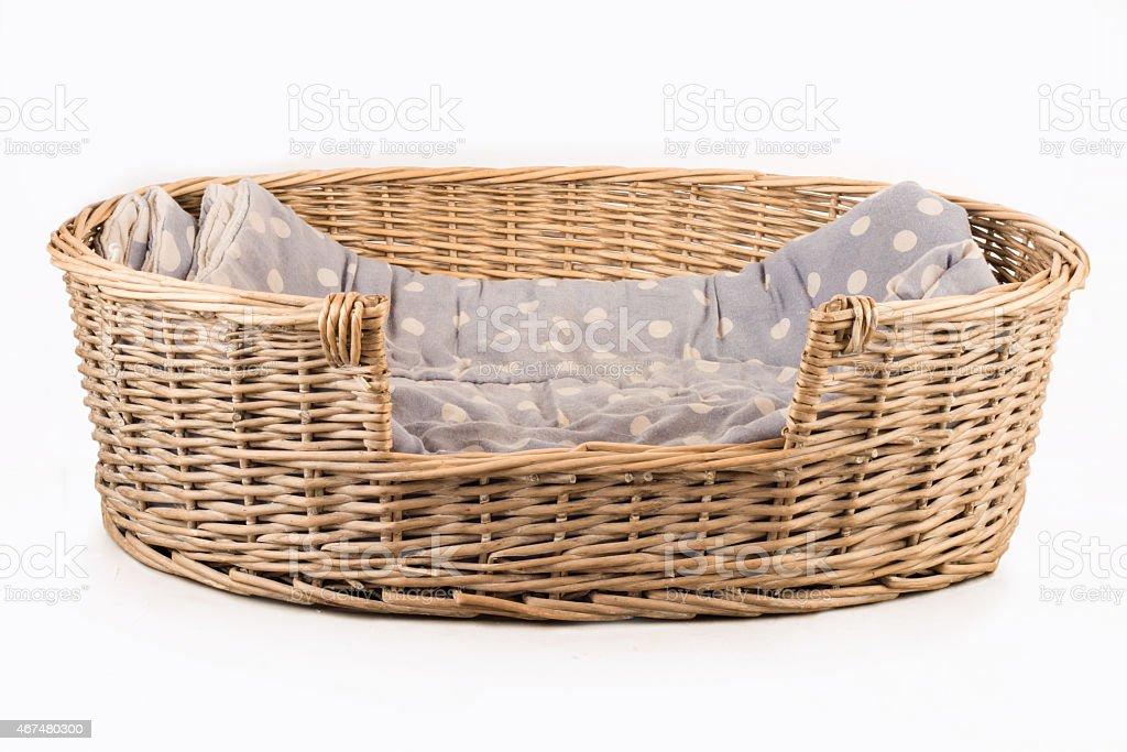Dog basket containing gray spotty blanket stock photo