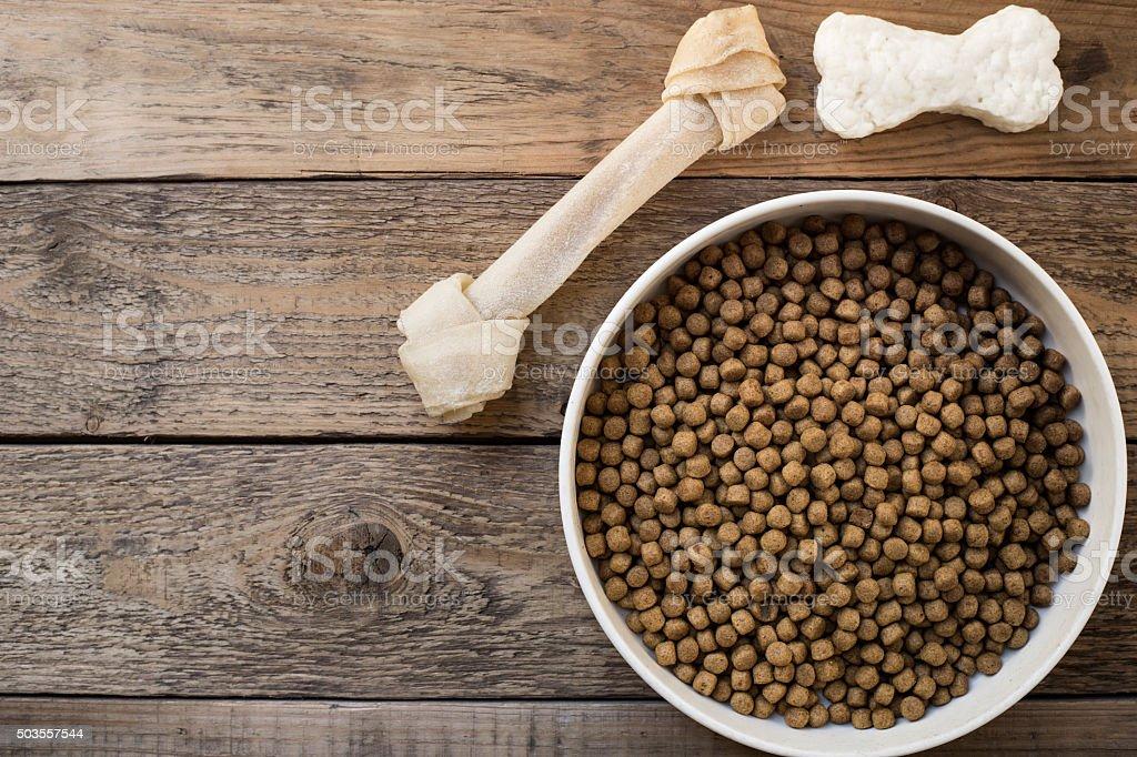 Dog bone and dog food on wood table stock photo