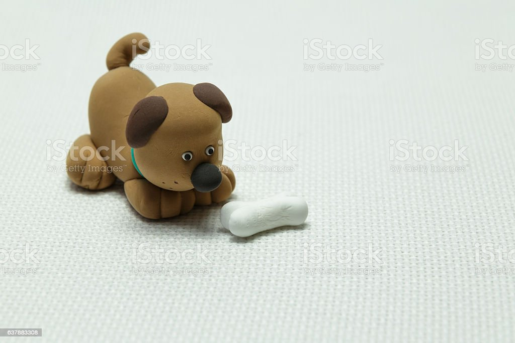 Dog from plasticine and a bone stock photo