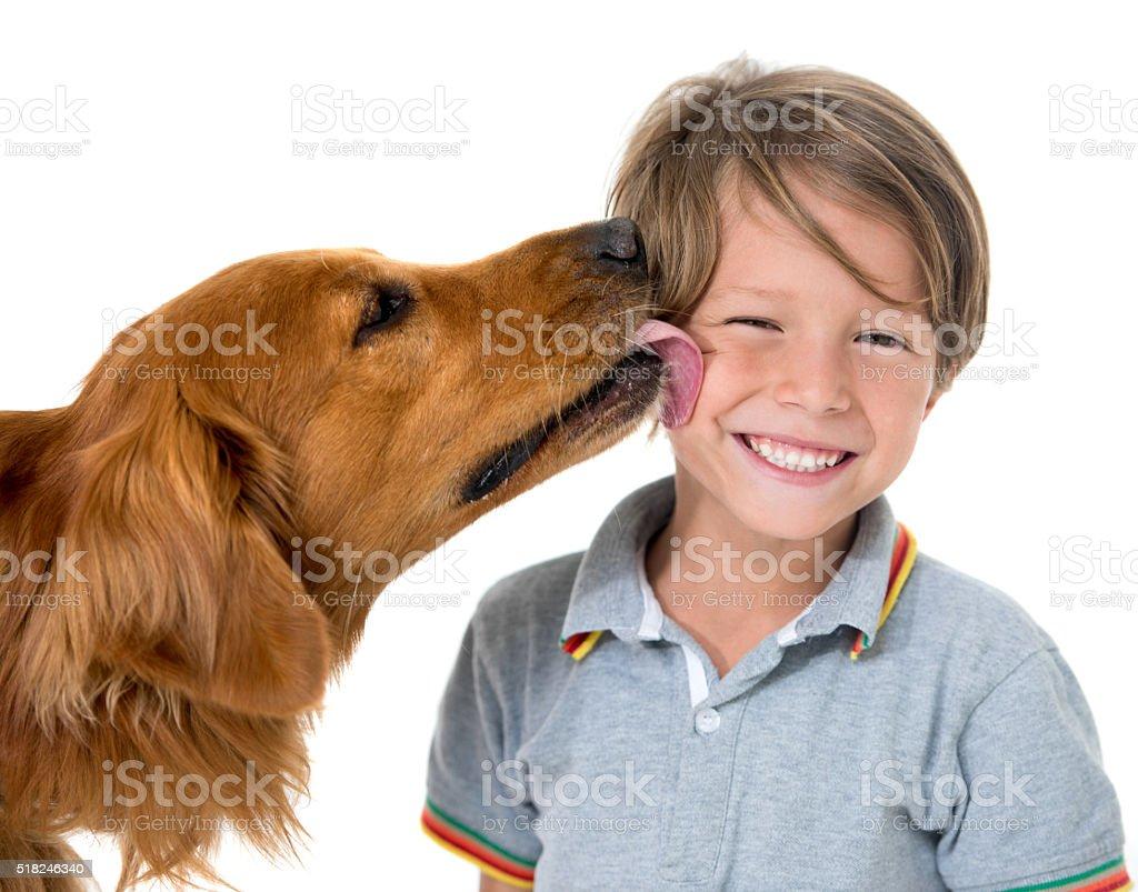 Dog kissing a happy boy stock photo