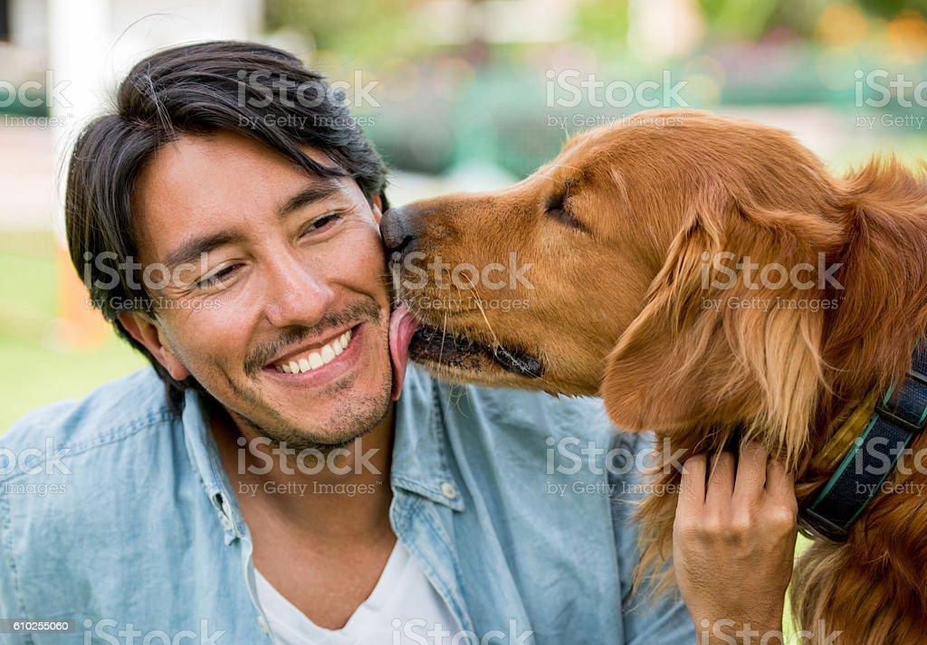 Dog licking a happy man stock photo